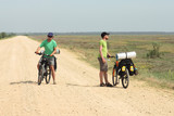 two men with bicycles in cycling trip standing on road, sky and poster
