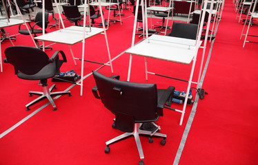 rows of black chairs, white tables and mirrors for hairdressers