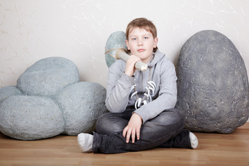 Teenager sits on laminate floor with stone ax