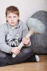Teenager sits on floor with unkind face with stone hammer