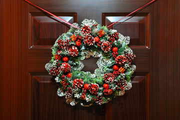 Artificial circled wreath with knops and bead hangs on door