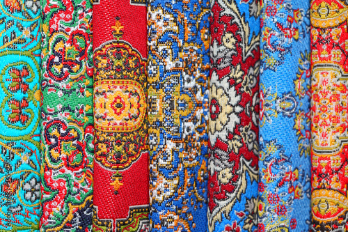 Seven varicoloured carpets lie in rouleau on each other