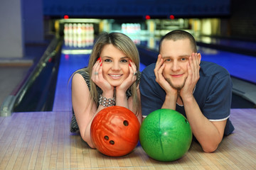 Couple lie on alongside, lean chin on hands in bowling club