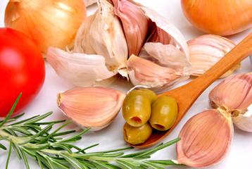 Oliven auf einem Löffel, Knoblauch, Zwiebel und Tomate