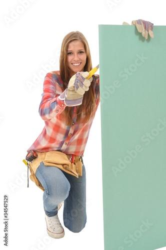 Handwerkerin bearbeitet Gipskartonplatte mit dem Messer