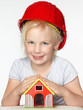 Cute little girl with helmet protecting her house