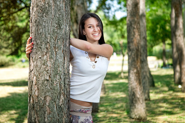 Happy young girl hides behind a tree in the park