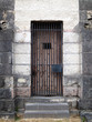 Old stone jail wooden door with iron bars