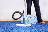 Vacuum cleaner in action-men cleaner a carpet.
