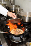 Chef is making flambe dish on restaurant kitchen