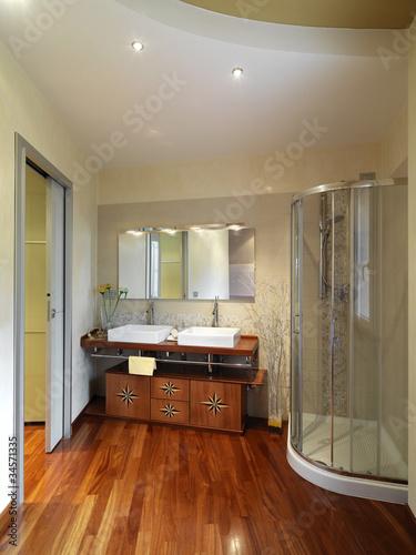 bagno moderno con intarsio nei mobili e pavimento di legno