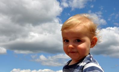 bébé blond garçon sur fond ciel bleu
