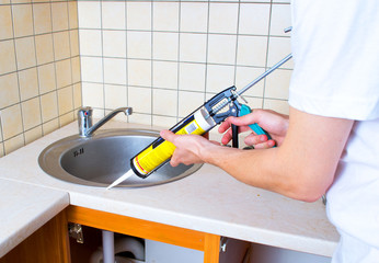 Caulking gun putting silicone sealant to installing a kitchen si