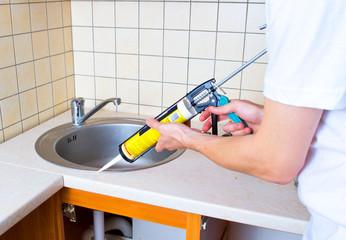 Caulking gun putting silicone sealant to installing a kitchen si