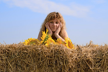 Girl is laying on sheaf hay at the field
