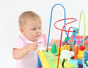 Cute baby girl playing with colorful toys