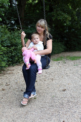 Young mother with daugther on swing