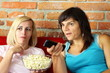 Two happy female friends eating popcorn and watching tv