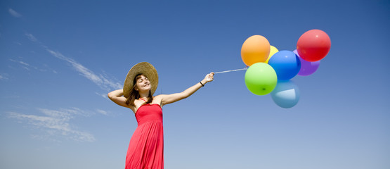 Brunette girl with colour balloons at blue sky background.