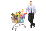 Man posing next to a shopping cart with groceries