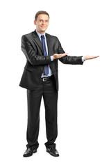 Man in suit gesturing welcome