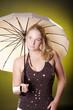 Natürliche Frau mit Regenschirm blickt in die Ferne