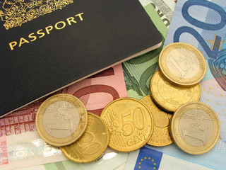Close up of Euro coins and bills surrounding a passport