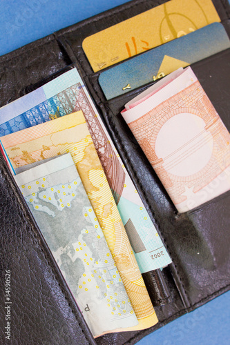 euro money and plastic cards in black wallet