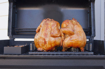 Two whole barbequed chickens on the grill