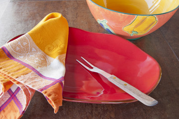 Colorful red platter and bowl with napkin and fork