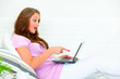 Confused pretty woman on couch and pointing finger at laptop