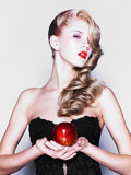 Young pretty woman in a fashionable dress with apple