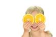 kleines Mädchen hält sich Orangenscheiben vor die Augen