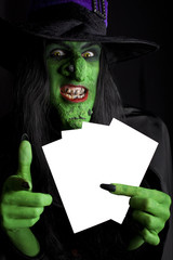 Evil green witch with space for text, black background.