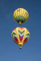Two hot-air balloons flying vertically aligned