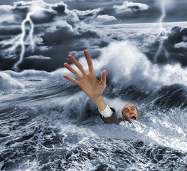 Businessman sinking in dark stormy sea