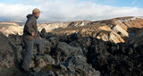 tourist looking on lava field at Landmannalaugar, Iceland poster
