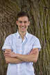 lächelnder junger Mann lehnt an einem Baum