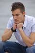 nachdenklicher junger Mann sitzt am Flussufer
