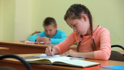 Little girl fulfilling written tasks in school