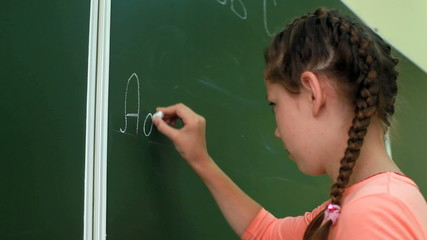 Little girl writing ABC on blackboard