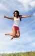 Jeune femme sautant au dessus d'un champ en été