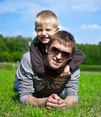 father with his son lying on the grass in the park, arm in arm