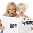 Very surprised mother and daughter reading newspaper together