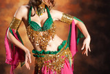 Fototapety Beautiful exotic belly dancer woman a rot-green costume