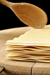 Lasagne sheets on wooden chopping board