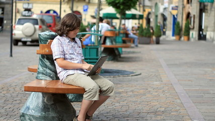 Young teenager with tablet computer sitting in the city