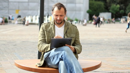 Young happy man with tablet computer sitting in the city