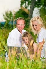 Glückliche Familie sitzt auf Wiese mit Laptop