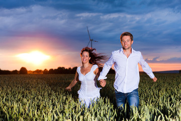 Couple is running over grainfield at night
